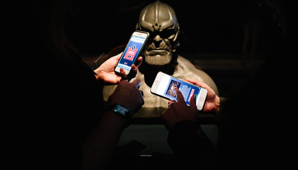 Marvel Mobile in use at GOMA. Users are interacting with a Thanos statue with the Marvel Mobiel app.