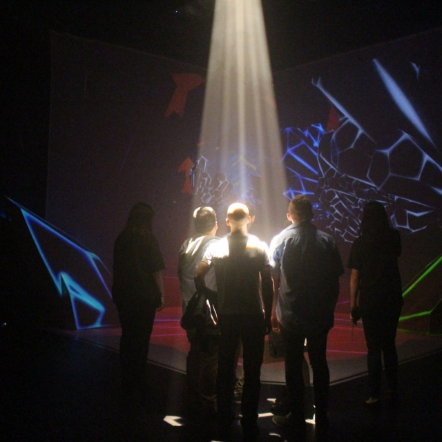 Stage of Colliding Dimensions with people viewing it under shaped light